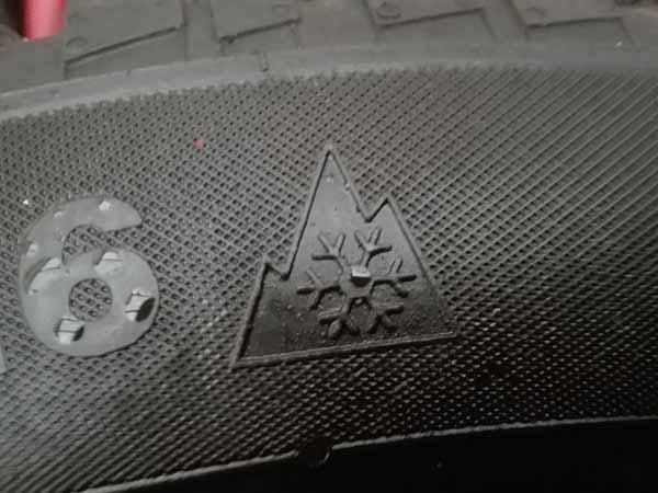 Zdjęcie fragmentu opony przedstawiające znaczek 3pmsf czyli tzw. śnieżynkę z górą w tle- symbol opony zimowej