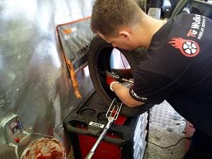 Na obrazku Mateusz Celej z TG Wulkan naprawia oponę